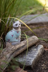 Cat Garden Figurine in Blue Shirt With Pink Roses in Flower Bed on Sunny Day - Vertical