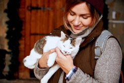Cat in the hands of girl volunteer, in shelter for homeless animals. Pets.