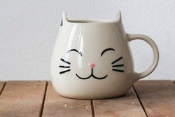 Cat shape cup on wooden table