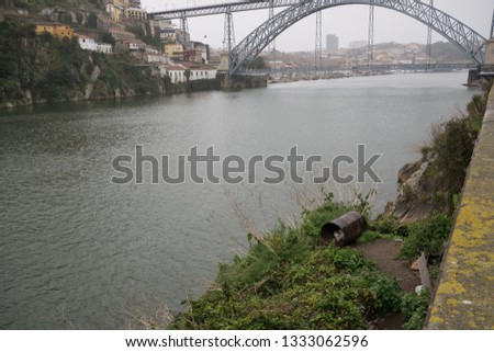 Cat shelters from rain in old metal barrel on banks of River Douro in Porto, Portugal with bridge in background #1333062596