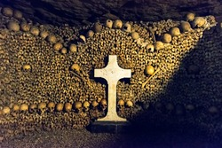 Catacombs of Paris, France. Famous Catacombs (Les catacombes de Paris) are underground ossuaries and tourist attraction. Unusual museum in the old dark dungeon. Scary tunnel with human bones.