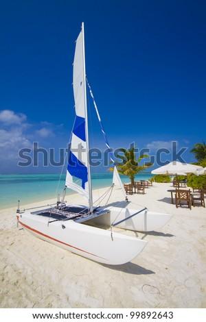 catamaran at a tropical beach, sunshade with table and chairs