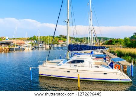 Catamaran boat anchoring in beautiful Seedorf marina on coast of Rugen island, Baltic Sea, Germany #1272696445