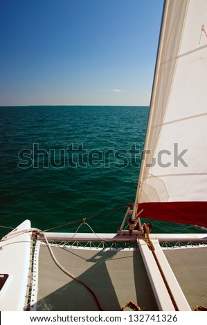 Catamaran sailboat with white and red set sail, sailing on a beautiful cloudless blue sky day and calm blue ocean waters