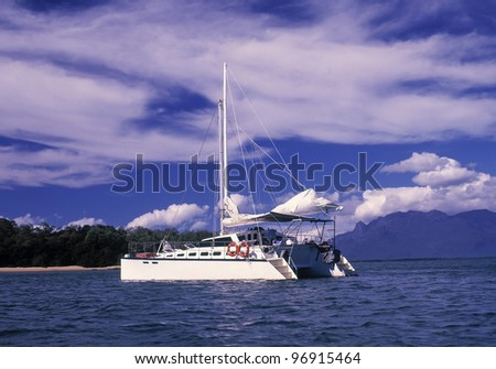 Catamaran sits quietly in a calm bay. - stock photo