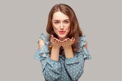 Catch my kiss! Lovely romantic brunette girl ruffle blouse looking at camera air kissing over palms hands, sending love. Beauty care and fashion vogue. indoor studio shot isolated on gray background