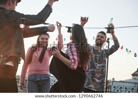 Catchy song. You can see it by gestures. Dancing party on the roof with beautiful sunshine at background. Young stylish people.