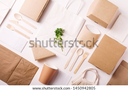 Catering and street fast food paper cups, plates and containers. Eco-friendly food packaging on white background with copy space. Flat lay. Top view. Carering of nature and recycling concept.