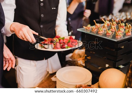 Shutterstock Catering banquet table at reception. Restaurant presentation, molecular gastronomy, haute cuisine, food consumption, party concept. Waiter serving strawberry.