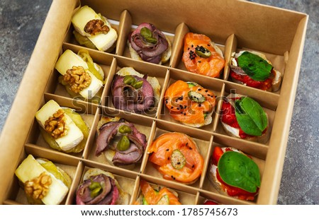 Catering food delivery in cardboard box for wine party.Delicious snacks delivered on venue in package for public event.Red fish fillet,veal meat,capers,brie cheese on canape bread for lunch meal Photo stock ©