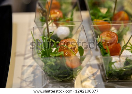 Catering: portions of mozzarella salad with rukola in little glass containers