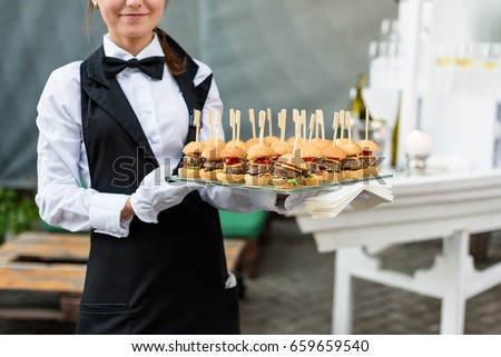 Catering service. Waiter carrying a tray of appetizers. Outdoor party with finger food, mini burgers, sliders.