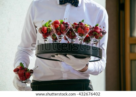 Catering service. Waiter carrying a tray of fruit cocktails with a strawberries and cherries