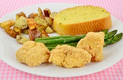 Catfish nuggets brushed with mustard then rolled in cornmeal and deep fried.  Served on white plate with home fries and asparagus and garlic bread.