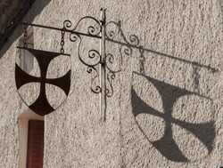Cathar cross and its shadow in a house of Rennes-Le-Château, France.