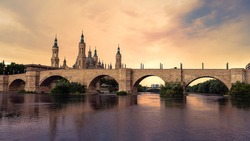 Cathedral Basilica of Our Lady of Pillar with bridge and the Ebro river at sunset. A Roman Catholic church in the old city center of Zaragoza. Landmark monument of Aragon region at north of Spain