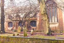 Cathedral crypts with scary mossy graveyard on the graves behind the cathedral with British Gothic architecture. Green graves in the rain scene good for Hallowee