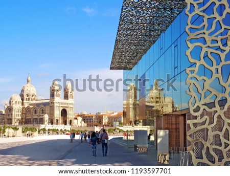 Cathedral de la Major in Marseille reflecting on a modern museum facade.