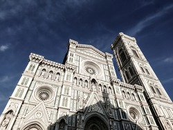Cathedral of Santa Maria del Fiore. Landmark 1200s cathedral colored marble facade and elegant Giotto tower close sunny view with blue sky background. Travel Italy. Color graded