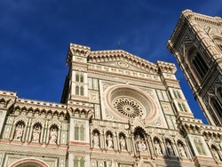 Cathedral of Santa Maria del Fiore. Landmark 1200s cathedral colored marble facade and Giotto tower close sunny view with blue sky background. Travel Italy