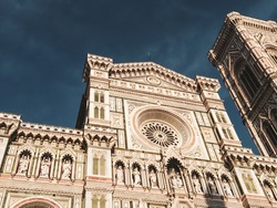 Cathedral of Santa Maria del Fiore. Landmark 1200s cathedral colored marble facade close sunny view with blue sky background. Travel Italy. Color graded