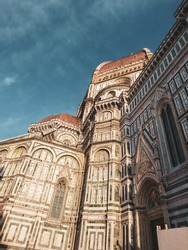 Cathedral of Santa Maria del Fiore. Landmark 1200s cathedral colored marble side facade sunny view with blue sky background. Travel Italy. Color graded