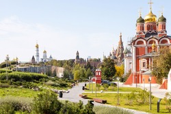 cathedral of Znamensky monastery in the Old Tsar's yard in Zaryadye urban landscape public park on Varvarka street and view of Kremlin on background in Moscow city on sunny September day