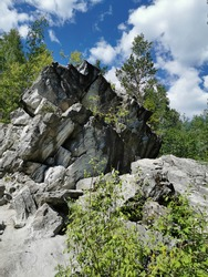 Catherine's marble cliff surrounded by trees in Ruskeala Mountain Park on a sunny summer day.