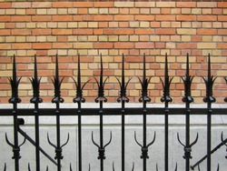 Catholic church garden with black ornate metal sharp fence and red bricks church wall in Budapest, Hungary