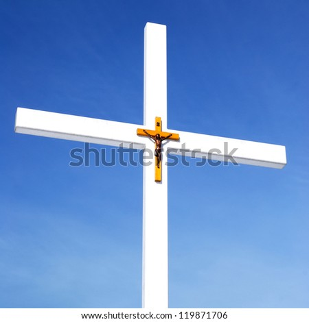 catholic cross with crucifixion sign against blue sky