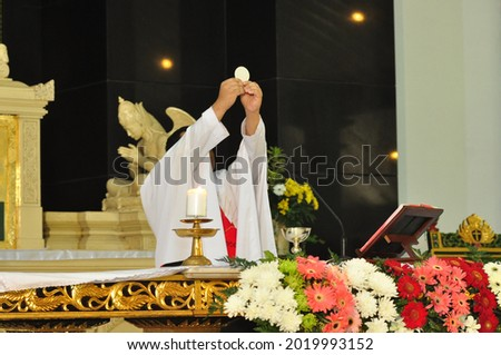 catholic mass - a priest lifts the host during a mass as a symbol of respect for the body of Christ