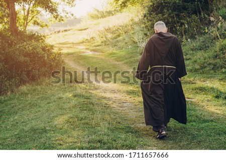 Catholic monk of the Capuchin Order, an adult wise man with a beard and in long dark brown clothing walks the stone path in the morning in nature Photo stock ©