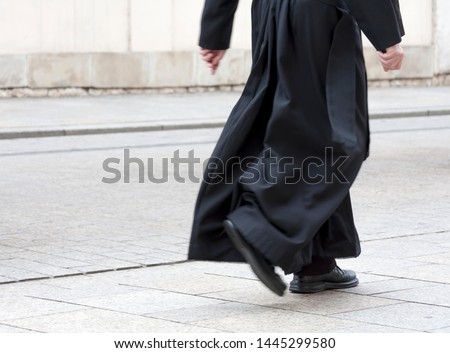 Catholic priest in the black cassock walking on the street solo, only legs visible. Clergy, faith, christianity and calling abstract concept #1445299580