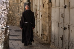 Catholic priest walking on the narrow stone street in the Old city of Jerusalem