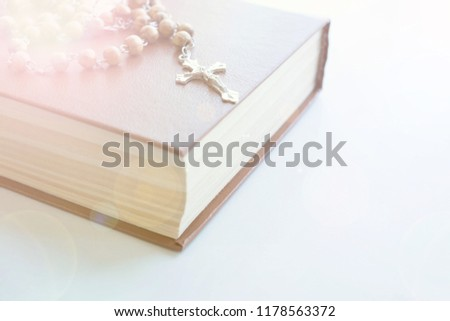 Catholic rosary beads with old book on cement table prayer, rosary background concept in vintage tone.