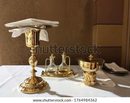 Catholic Sacristan mass item: Chalice, Ciborium, Purificator, Pall and Holy water and Holy wine before the mass at a Catholic Church.low light background.