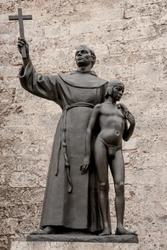 Catholic Saint Junipero Serra (1713-1784) religious statue in the Saint Francis of Assisi square in old Havana, Cuba. Catholic figure holding a a Christian cross and a young boy.