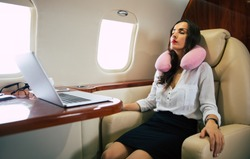 Catnap in the flight. A calm woman in formal clothes is taking a nap in her armchair, sitting near the desk with a laptop on it, while taking a flight on a business class plane.