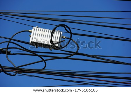 CATV system hanging on black optical fiber cables for amplify TV signals installed with coaxial cables. Concept of CATV system, amplify TV signal.                              ストックフォト ©