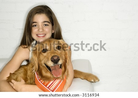 Caucasian adolescent girl holding Golden Retriever dog.