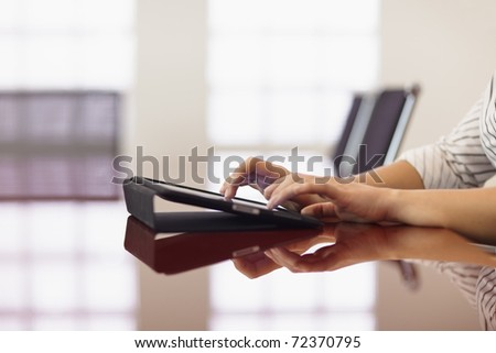 caucasian adult female assistant typing on tablet pc in meeting room. Horizontal shape, side view, copy space
