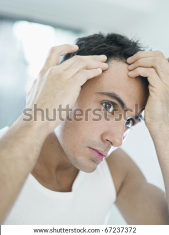 caucasian adult man checking hairline. Vertical shape, head and shoulders