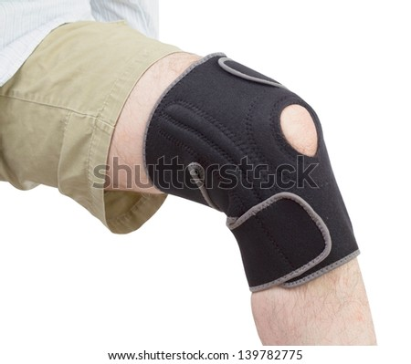 Caucasian adult putting on neoprene knee brace isolated on white background.