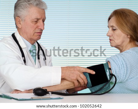 Caucasian aged doctor with a elderly patient on a light background