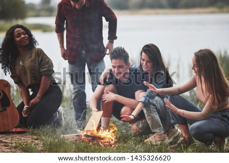 Caucasian and african american ethnicities. Group of people have picnic on the beach. Friends have fun at weekend time.
