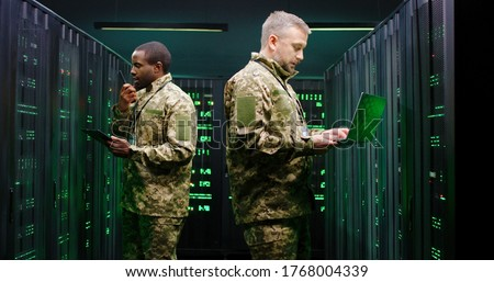 Caucasian and African American men in camouflage uniforms working in server room and checking data with tablet device and laptop computer. Mixed-races army forces co-workers Walkie-talkie info passing