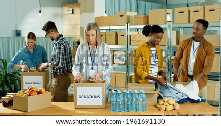 Caucasian and African American people men and women volunteers working at charity organization packing clothes and food grocery in donations box. Volunteering, social help for poor and needy Stock photo ©