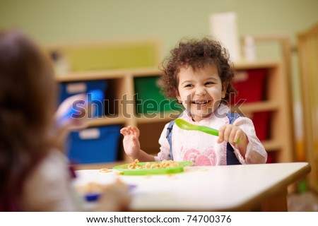 Caucasian and hispanic female preschoolers eating pasta and smiling. Horizontal shape, waist up, focus on background