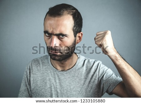 Caucasian angry man on gray background. #1233105880