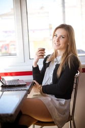 Caucasian attractive woman working using mobile smart phone and laptop drinking coffee in restaurant background. Text messaging, online banking, playing game, watching video or e commerce shopping